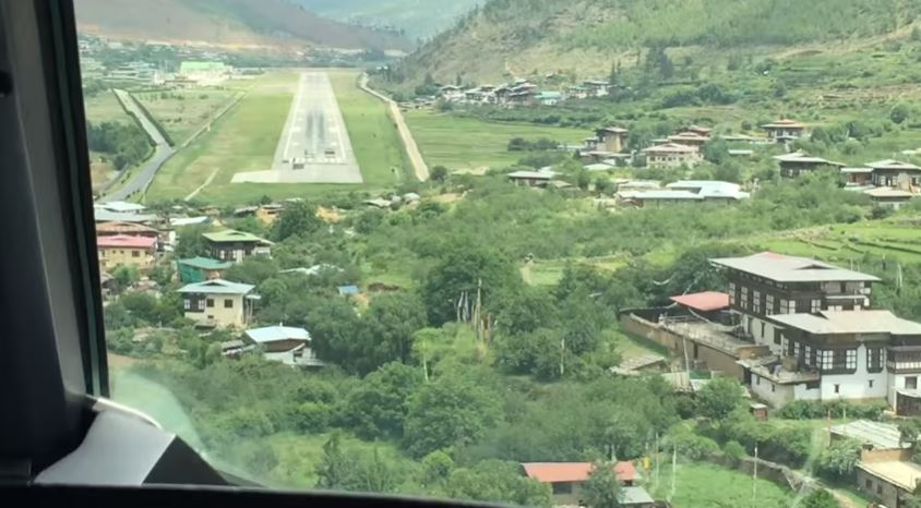"""Resultado de imagen para En 1968, India construyó una peligrosa pista de aterrizaje en el valle de Paro, inicialmente utilizada para operaciones de helicópteros por parte de las Fuerzas Armadas. En la actualidad, solo 17 pilotos están cualificados para aterrizar en uno de los aeropuertos más difíciles del planeta.    Y es que su situación, no tanto su pequeña pista, son un quebradero de cabeza para cualquier piloto experimentado. El aeropuerto se encuentra en lo profundo de un valle a 2.235 metros sobre el nivel medio del mar y está rodeado de montañas de picos de hasta 5.500 metros.    Se construyó con una pista de 1.200 metros de longitud, una de las más cortas por su elevación sobre el nivel del mar, lo que automáticamente estableció unos requisitos específicos del gobierno de Bután para la elección de los aviones que operaban desde Paro.    Los aviones tienen que atravesar las docenas de casas que se encuentran dispersas en la ladera de la montaña, llegando, literalmente, a pocos metros de los tejados. A ello se suman los fuertes vientos que azotan los valles, lo que a menudo resulta en una fuerte turbulencia.    La misma Boeing ha explicado que el aeropuerto es """"uno de los más difíciles del mundo para despegues y aterrizajes"""". De hecho, actualmente solo permiten a 17 pilotos cualificados el aterrizaje de una pista cuya situación la hace única.    Y es que el principal problema es que la pista está completamente fuera de la vista para los pilotos hasta el último minuto, ya que maniobran entre montañas en un ángulo de 45 grados antes de caer rápidamente en la pista.    Hay un punto en el que la parte inferior del avión se acerca peligrosamente a las casas de la cima de la montaña, una casa roja junto al acantilado es el punto focal clave para los pilotos que se acercan.    Los vuelos solo están permitidos durante el día y bajo condiciones meteorológicas visuales: estrictas tolerancias de luz en las que el piloto debe emitir su juicio a ojo en lugar de confiar en """